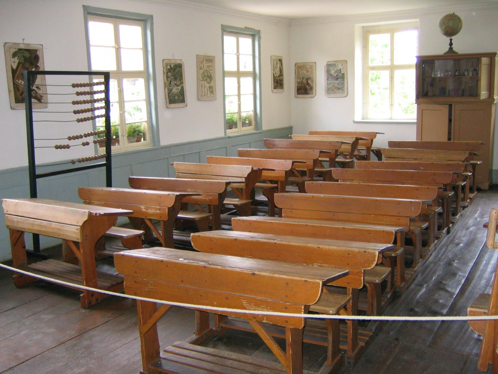 Sehr alter Klassenraum mit Holztischen.