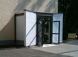 Eingang der Apostelkirche in Bonn Tannenbusch: weißer Vorbau mit gläserner Doppeltür. Ein buntes Kirchenfenster an Stelle der rechten Wand lässt viel farbiges Licht herein