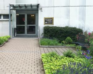 Hochhauseingang mit Blumen und Bänken vor der Tür in Bonn tannenbusch