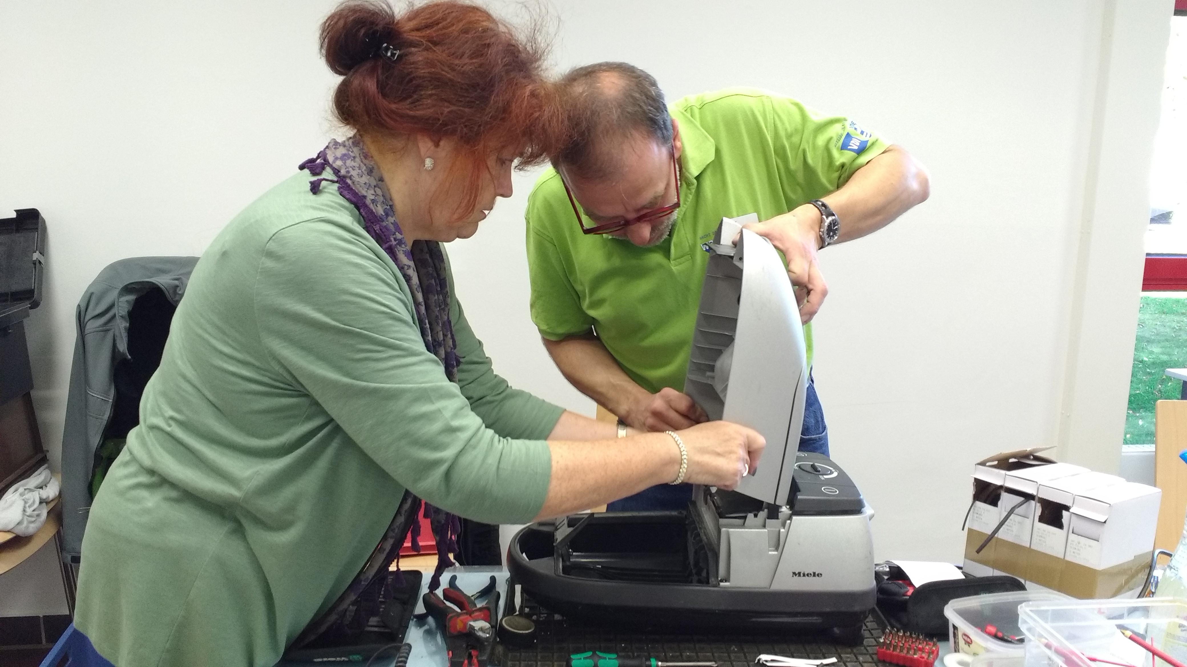Ein Mann und eine Frau reparieren gemeinsam einen Staubsauger